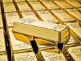 Gold bar on stacks of gold bullions close up