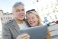 Senior couple using digital tablet in touristic area